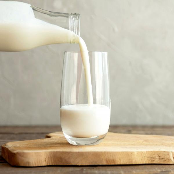 Milk pouring from glass bottle into glass on brown chopping board
