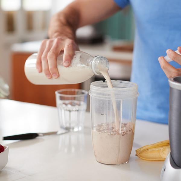 Man pouring protein shake into glass
