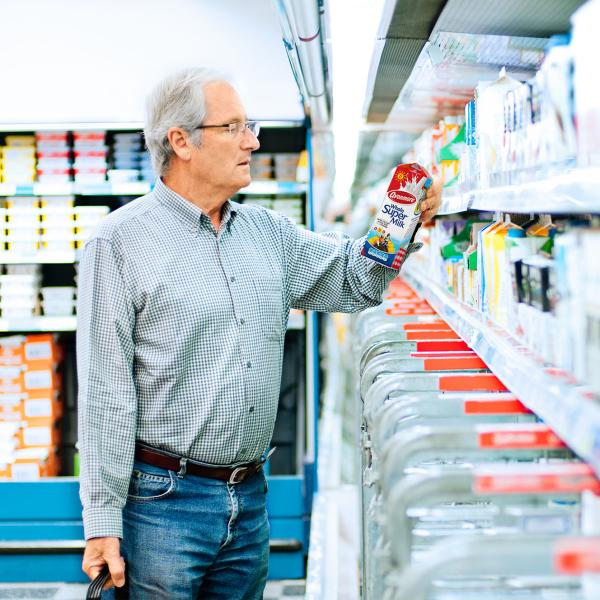 Elderly man reviewing the nutritional content of a carton of Avonmore Supermilk