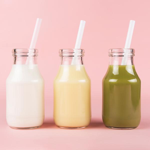 Three meal replacement drinks of different colours in small glass bottles