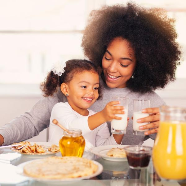 Mother and daughter at breakfast table each with a glass of milk