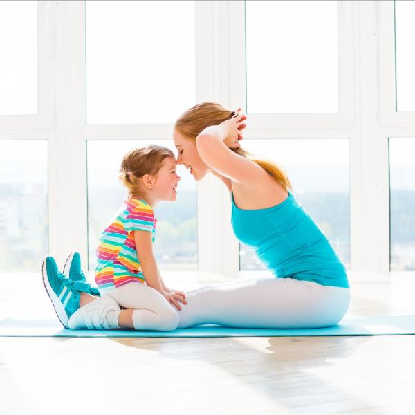 Woman doing exercise with her child watching