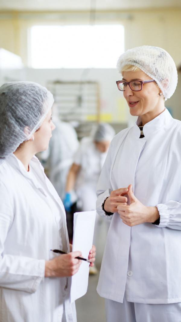Two women in a  factory discussing ingredients