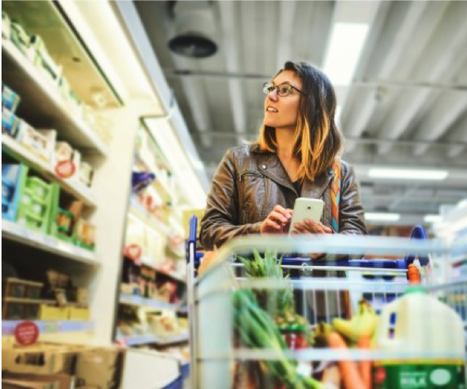 Image of woman shopping in grocery store. She is holding a phone, looking at the dairy aisle.
