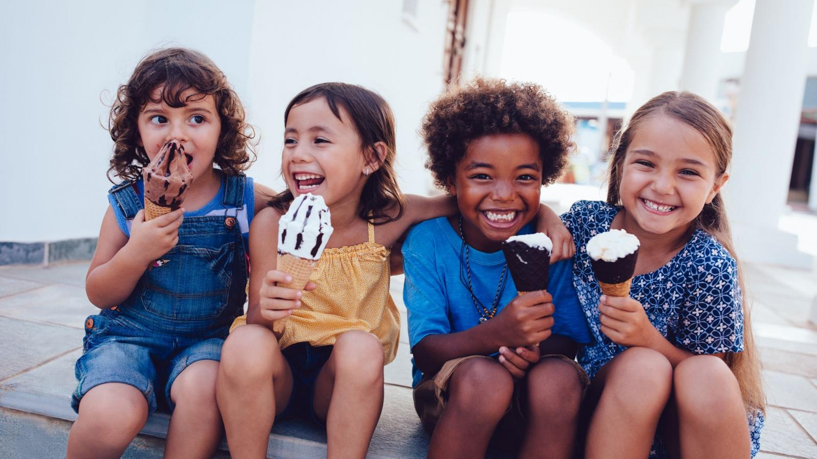 Four children sitting on a step and eating ice cream