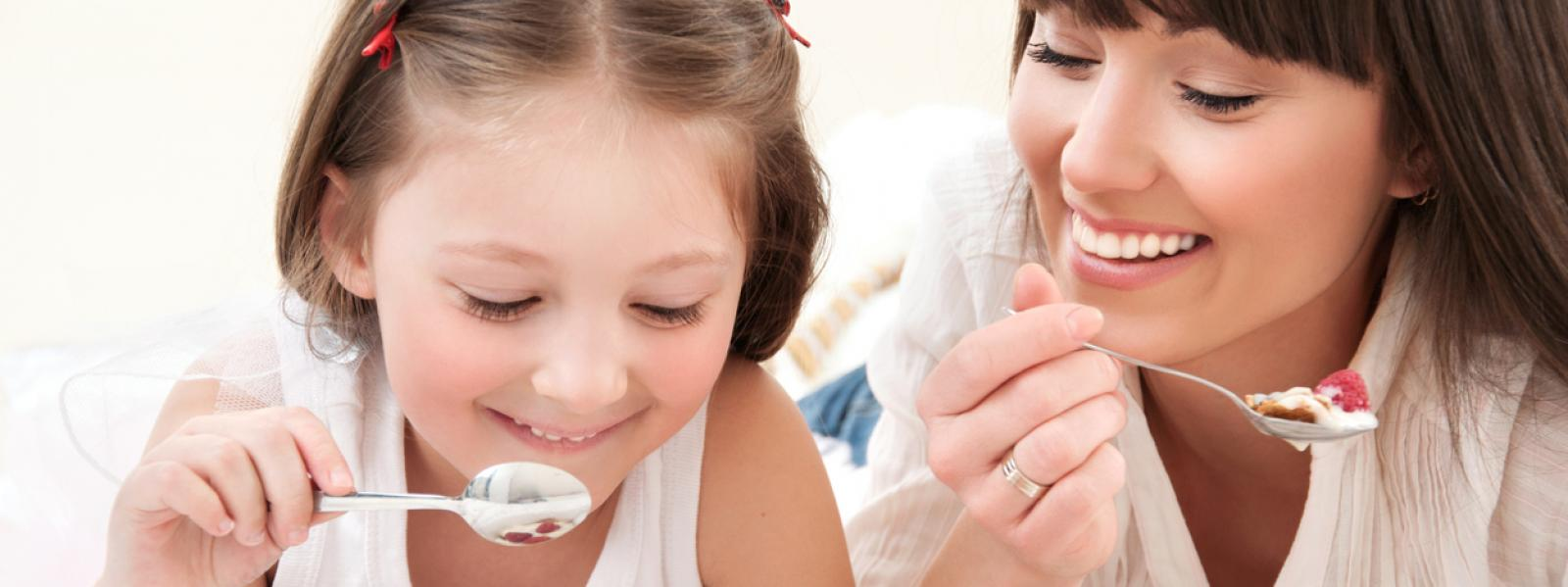 Static image of a mother and daughter smiling and eating yoghurt.